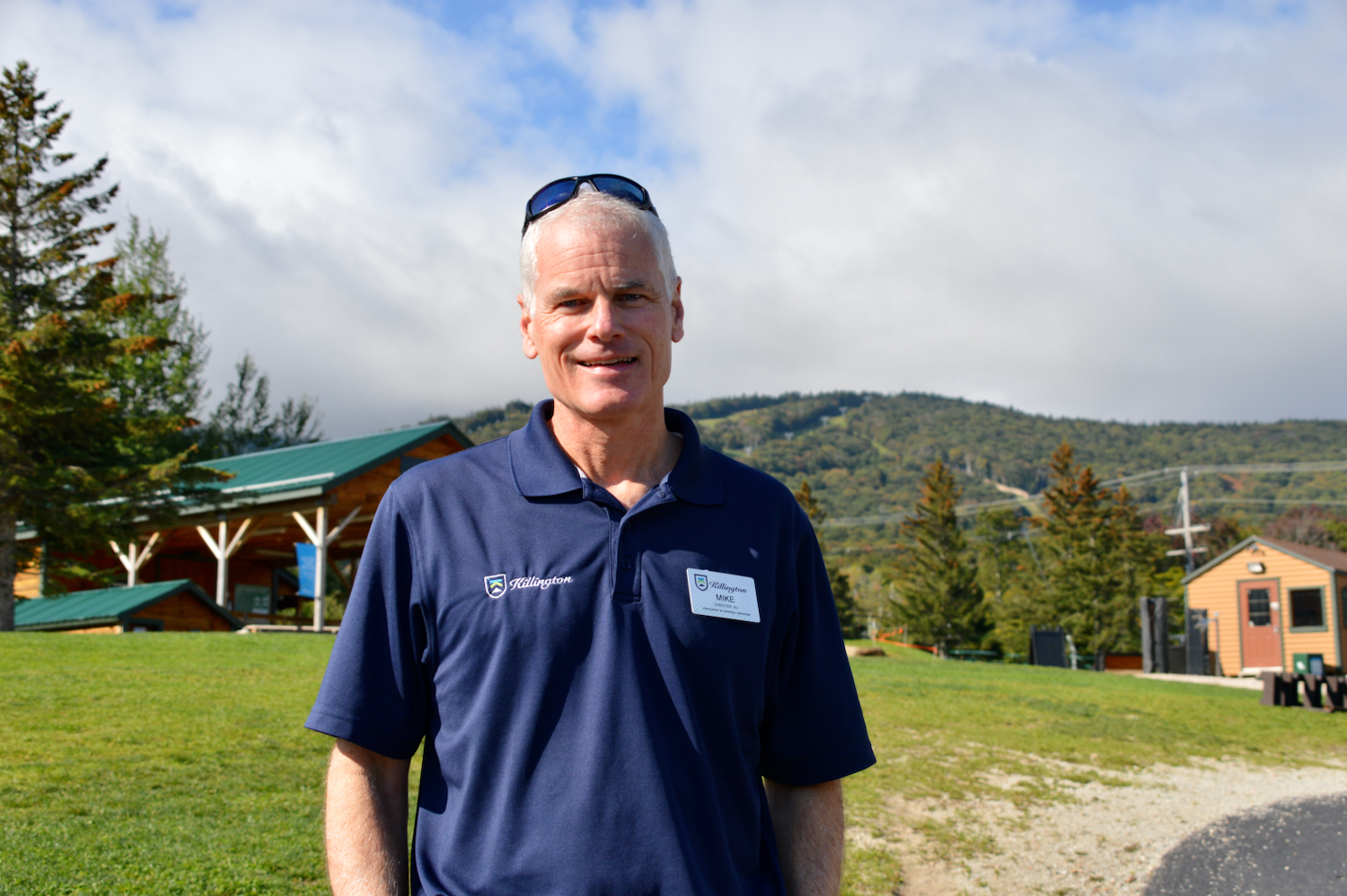 A photo of Mike Solimano, dressed in a blue sport shirt with sunglasses on his head, standing at the base of Killington ski resort.