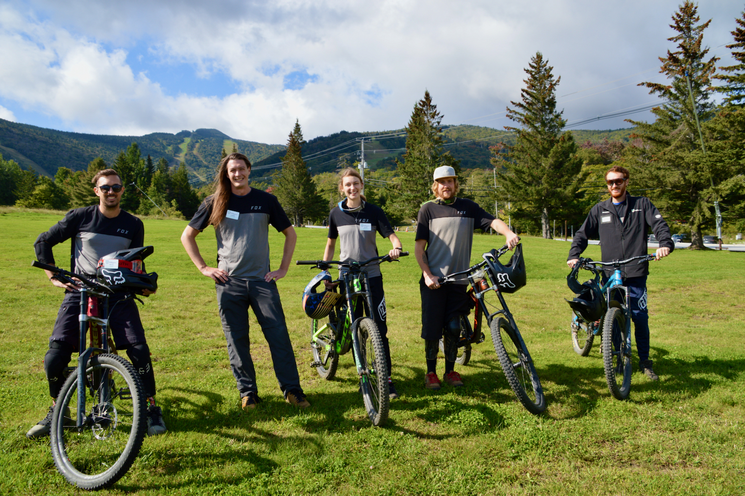 A photo of five mountain bike instructors posing in gray and black shirts with their bikes near the base of Killington.