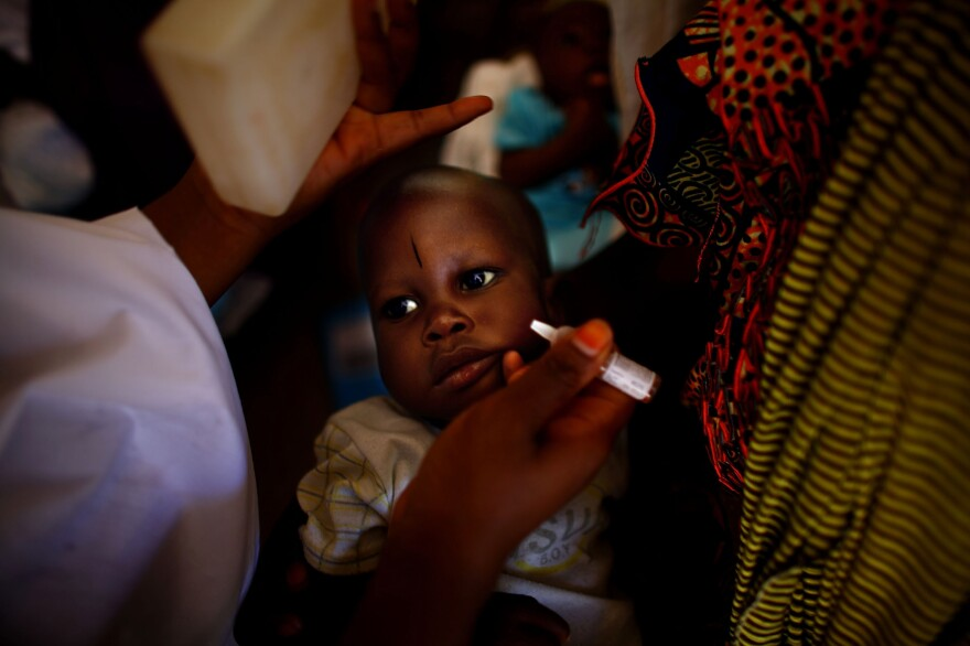 At the health clinic in Minjibir, two drops of vaccine are dropped into a child's mouth during a 2012 campaign.