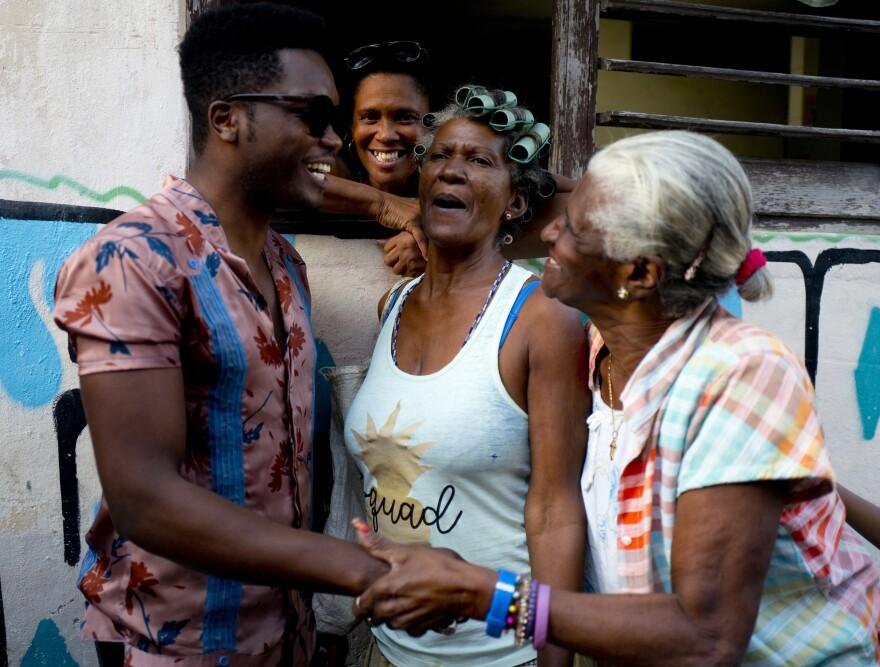 Cuban singer Erik Iglesias Rodriguez (left), who performs as Cimafunk, talks with women on the street in Havana.