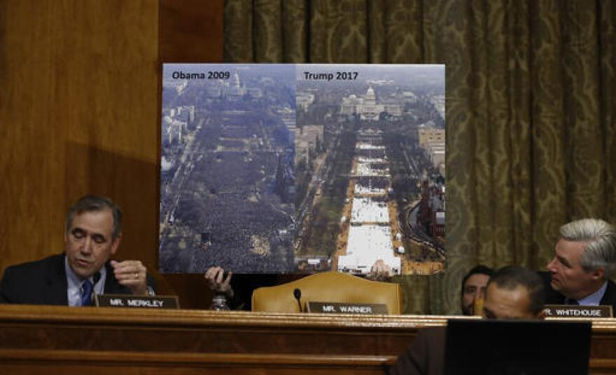 Senate Budget Committee members Sen. Jeff Merkley, D-Ore. (left), and Sen. Sheldon Whitehouse, D-R.I., flank a photograph showing inauguration crowd sizes in 2009 (left) and 2017.