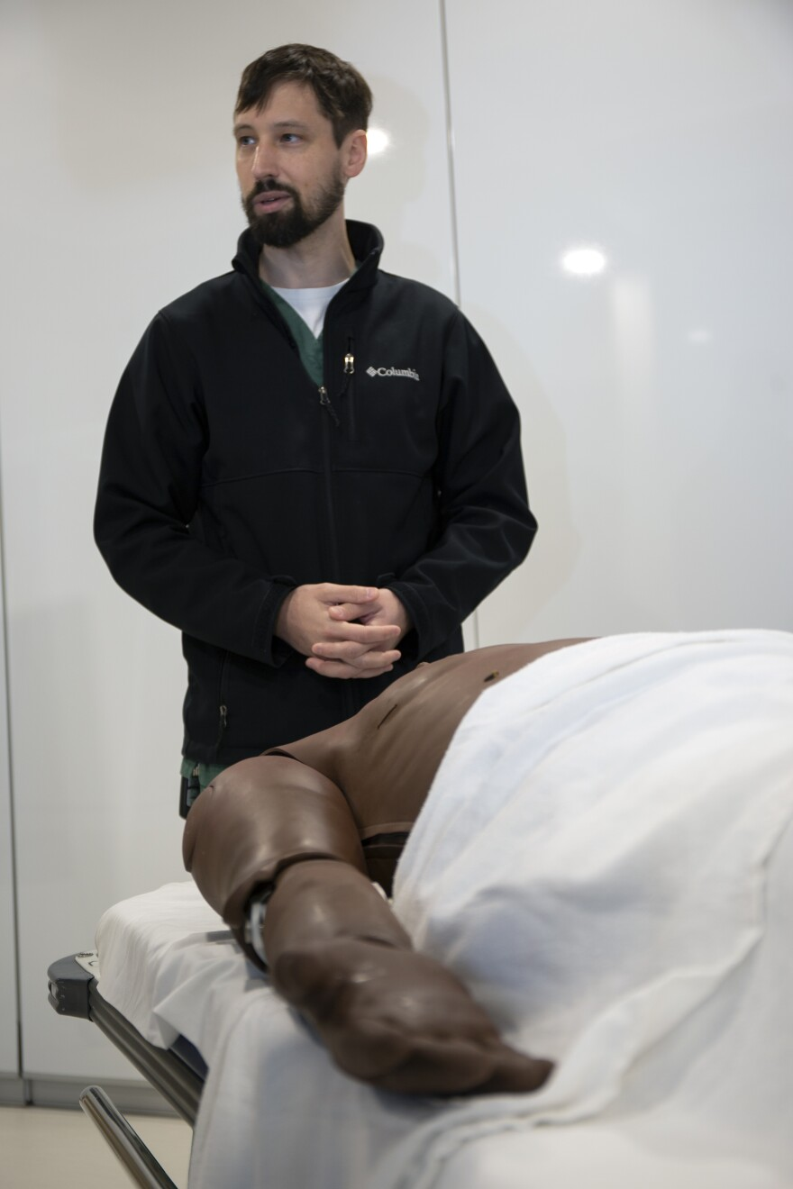 man stands over patient simulator