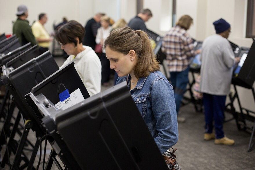 A woman casts her vote using an electronic voting machine.