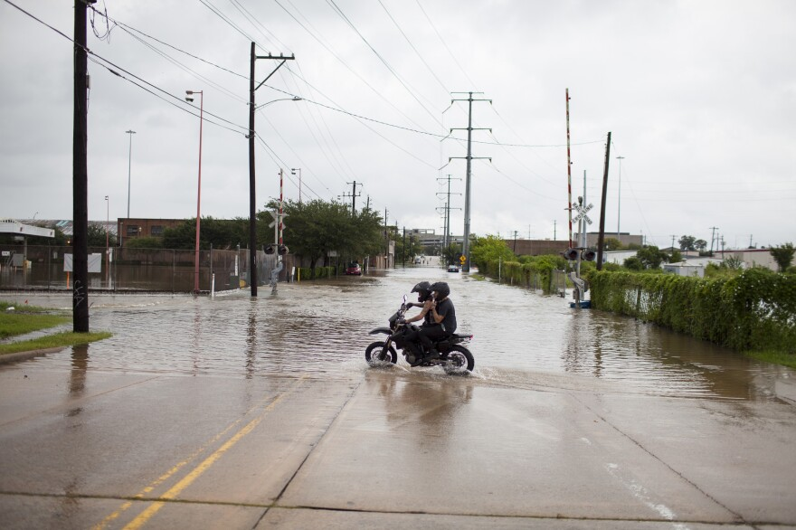 Reagan Giles, driving, and his friend Crusty Chuck turn around after deciding that they could not pass through a flooded street. Earlier in the day, Giles used his motorcycle to rescue Chuck from the Sunnyside neighborhood of Houston.