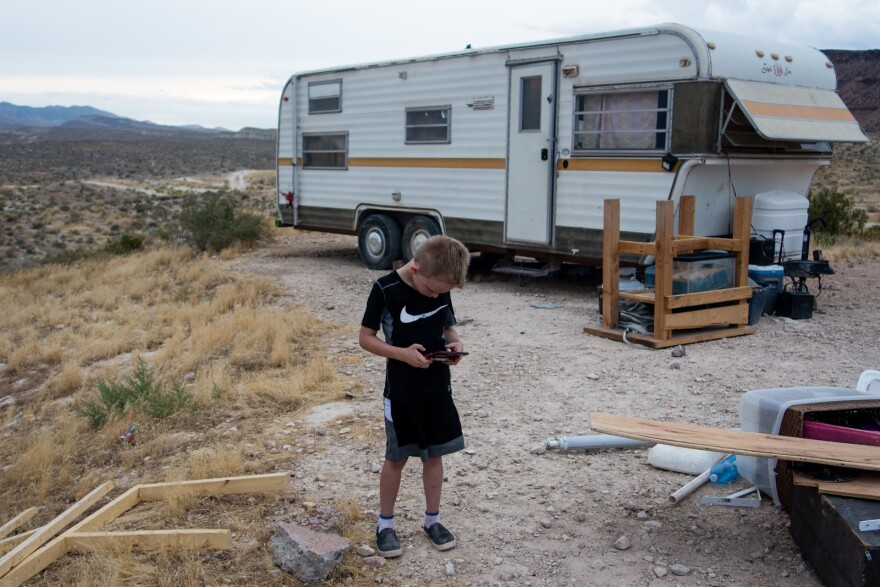 Phot of a boy playing a handheld video game in front of an old camper trailer. The desert stretches out in the background.