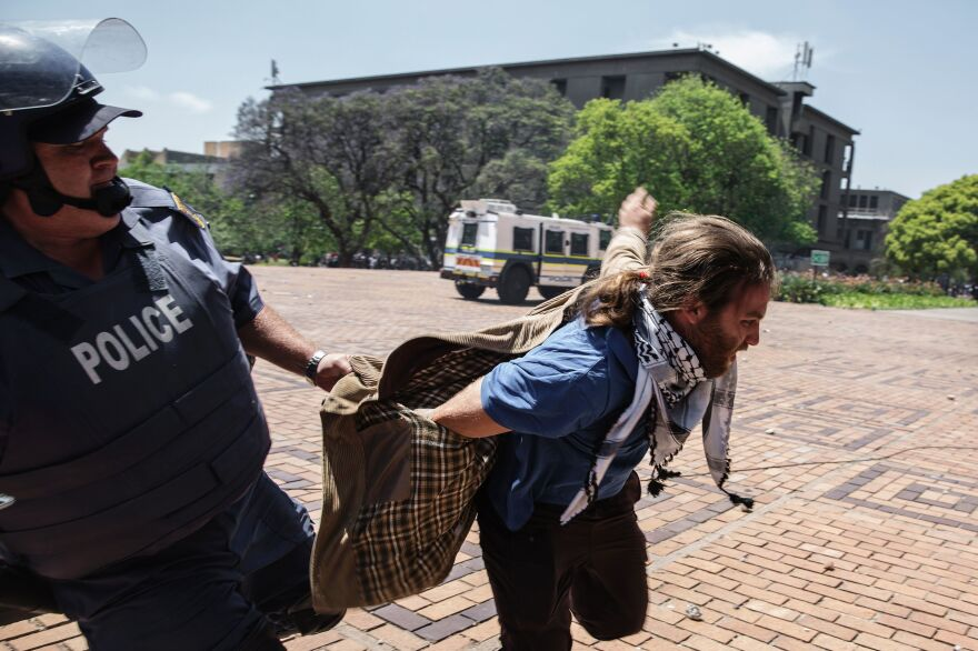 A South African policeman unsuccessfully tries to apprehend a student from the University of the Witswatersrand, also known as Wits University, on Monday. Student protesters at the prestigious university forced their way into lecture halls and caused many lessons to be abandoned, ratcheting up pressure in a battle over tuition fees.