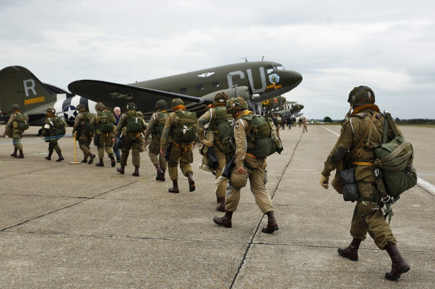 Members of the World War II Airborne Demonstration Team walk down the flight line at the Imperial War Museum Duxford on Tuesday.
