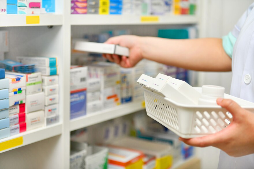 Photo of a person stocking a shelf at a pharmacy