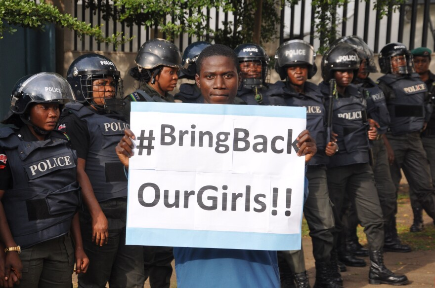 A man poses with a sign in front of police officers in riot gear during a demonstration calling on the government to rescue the kidnapped girls of a government secondary school in Chibok, in Abuja, Nigeria, on Tuesday.