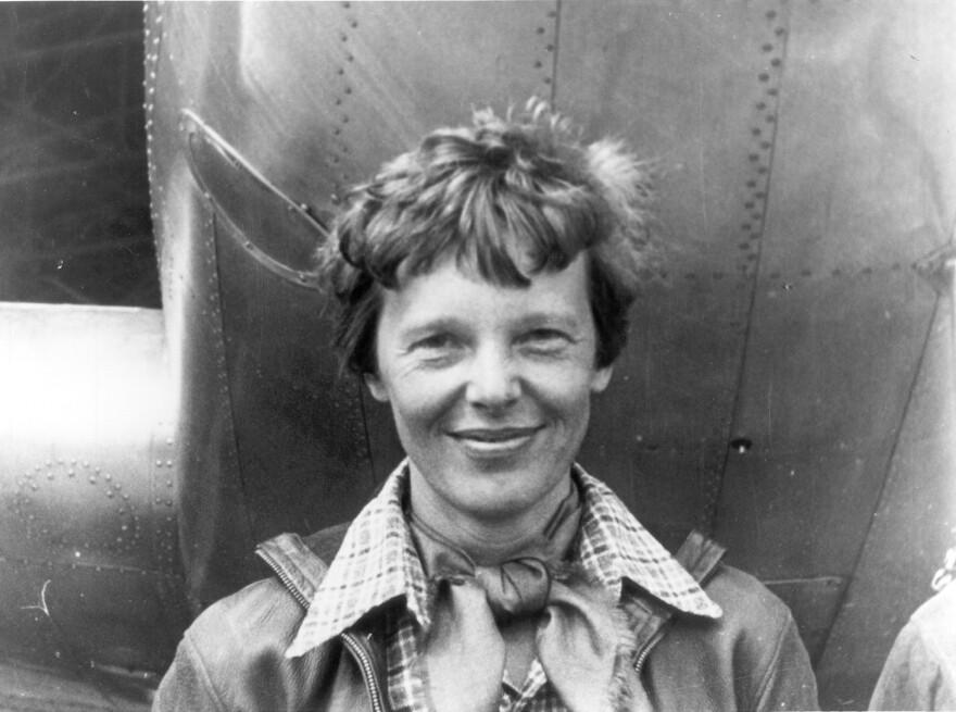 Amelia Earhart stands under the nose of her Lockheed Model 10-E Electra.