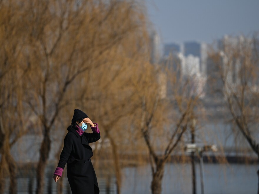 A woman walks in a park along Yangtze River in Wuhan on January 19, 2021. Residents of the city of 11 million, which was the first epicenter of COVID-19, have conflicting emotions as they reckon with the aftermath of the virus and their 76-day lockdown.