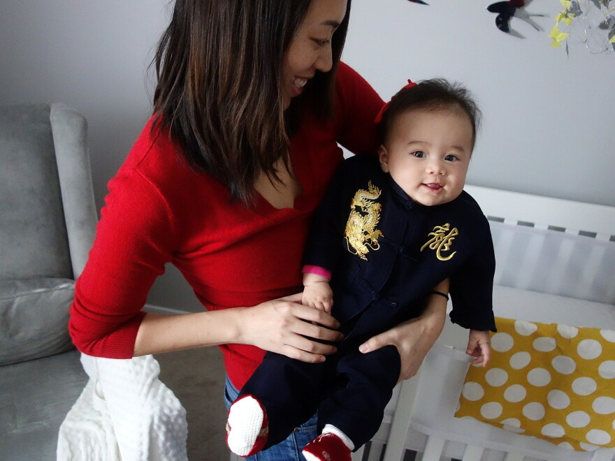 """The journalist with her half-Chinese daughter, Eva, on the Lunar New Year. Eva's outfit says """"dragon"""" in Chinese."""