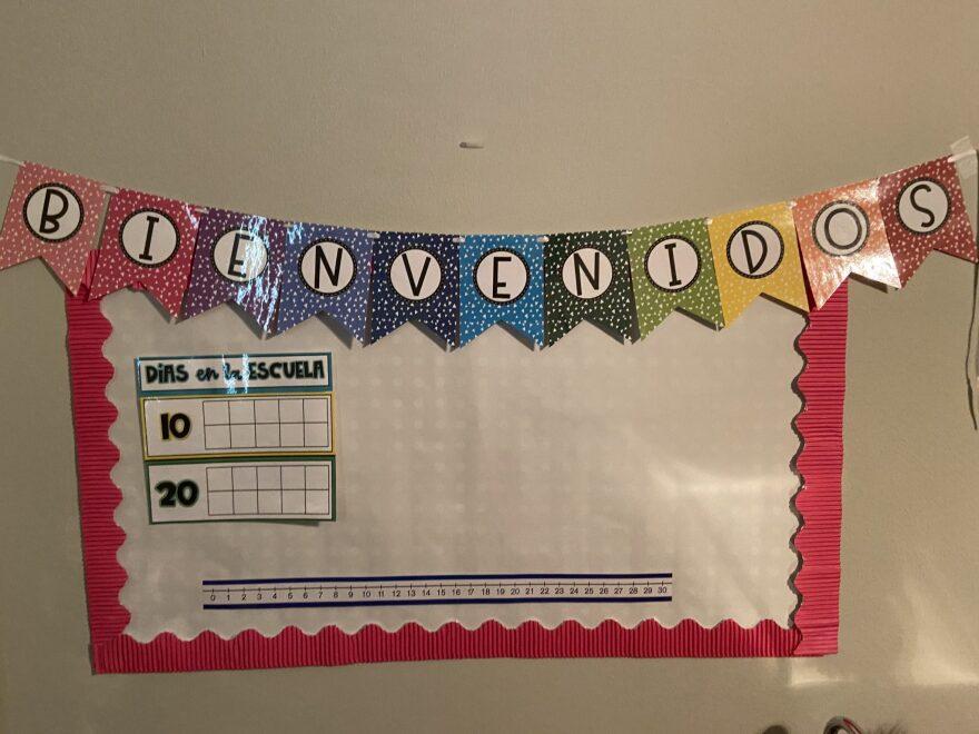 "A homemade banner reads ""Bienvenidos"" above a school teacher's home classroom setup for elementary students."