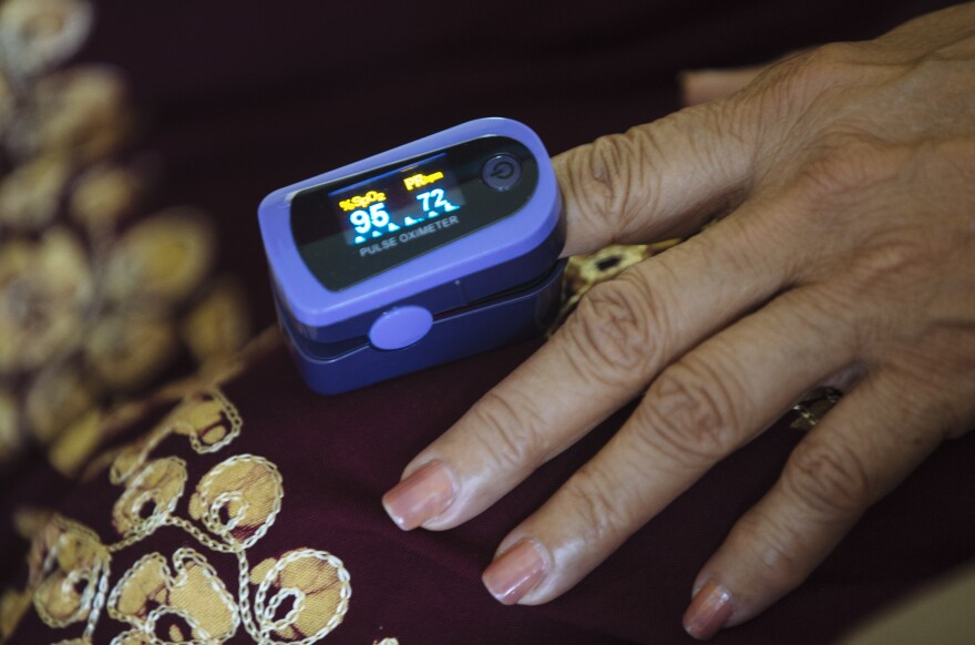 A paramedic used a pulse oximeter to check a patient's vital signs during an August home visit in the Bronx borough of New York.