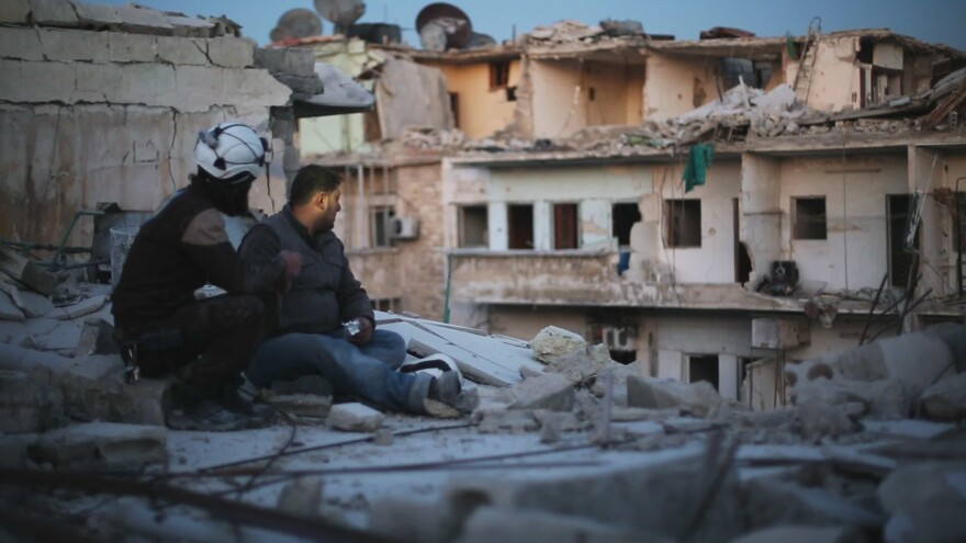"""Two members of """"The White Helmets"""" pause to take stock in the documentary <em>Last Men in Aleppo.</em>"""