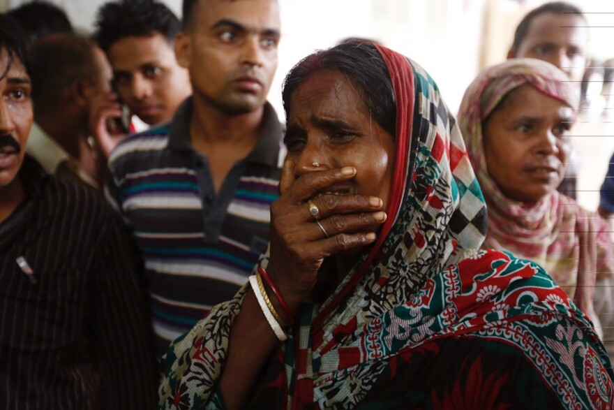A relative of a victim cries as bodies are carried into a makeshift morgue at a hospital after a fire broke out Saturday at a packaging factory in Tongi industy area outside Dhaka, Bangladesh.