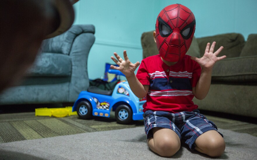 In this July 26, 2018 photo, a four-year-old boy is shown playing in a Spiderman mask, who is being cared for by Evelyn Zepeda at her home in Austin, Texas.