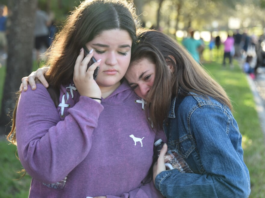Students use their phones following the shooting at Marjory Stoneman Douglas High School in Parkland, Fla.