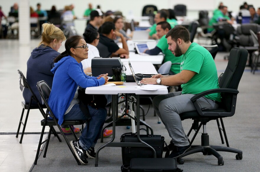 Juana Rivera (left) speaks with agent Fabrizzio Russi about buying insurance through the Affordable Care Act in Miami in 2014.