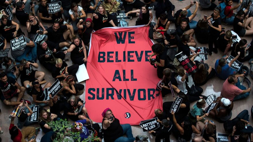 """Protesters unfurl a sign reading, """"We believe all survivors,"""" as they occupy the Hart Senate Office Building Thursday during a rally against Kavanaugh."""