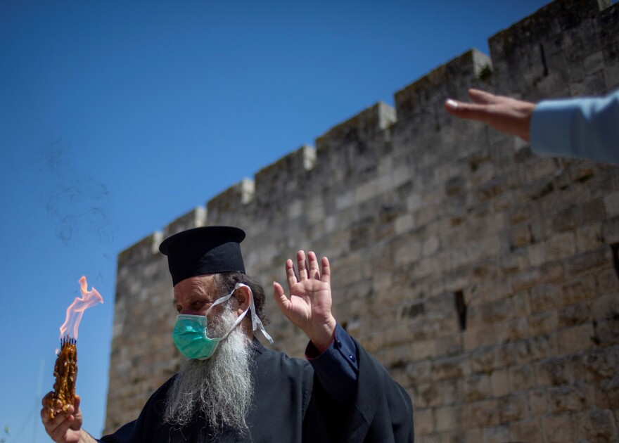 An Orthodox clergyman holds holy fire to transfer to predominantly Orthodox countries from the Church of the Holy Sepulchre, traditionally believed by many Christians to be the site of the crucifixion and burial of Jesus Christ. In Jerusalem's old city the traditional Holy Fire ceremony was called off amid coronavirus on Saturday.