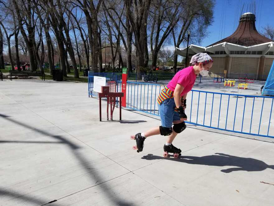 woman in park rollerskating with mask
