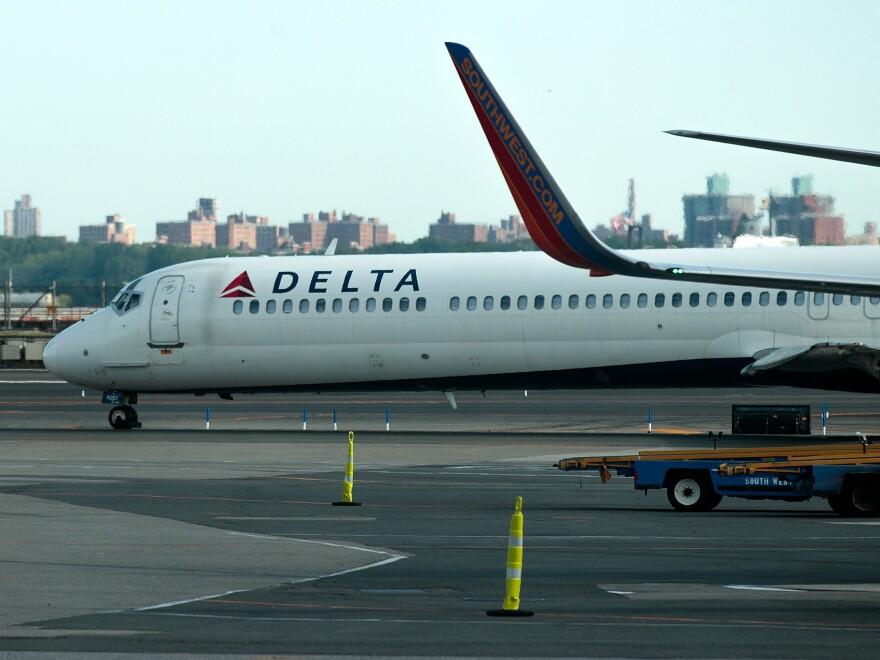 A Delta jet taxis on the tarmac at New York's LaGuardia Airport. About 1,000 Delta flights around the globe were canceled Monday, and hundreds more on Tuesday, after a system outage.