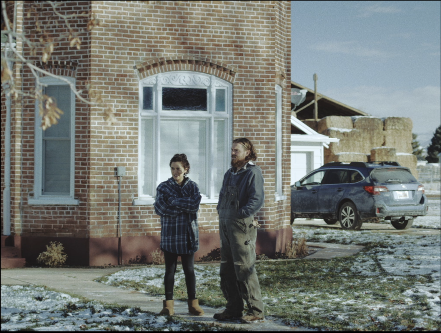 "Photo of two actors standing in front of a house in the film ""The Killing of Two Lovers"""