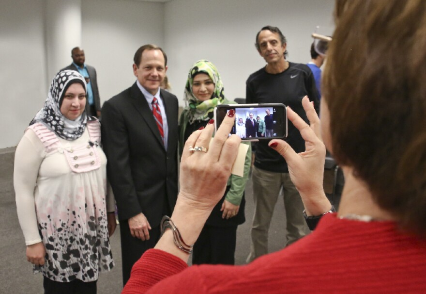 Basmah Alsaad, left, and Weam Alga asked Anna Crosslin, president and CEO of the Institute, right, foreground, to take a photo of them with St. Louis Mayor Francis Slay and their Institute English teacher, Les Meyer.