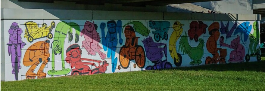 Palladino's mural extends around the corner of the underpass, including people and animals on bikes, scooters, and skateboards.