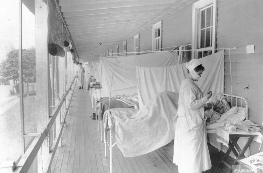 In this November 1918 photo made available by the Library of Congress, a nurse takes the pulse of a patient in the influenza ward of the Walter Reed hospital in Washington. (Harris Ewing/Library of Congress via AP)