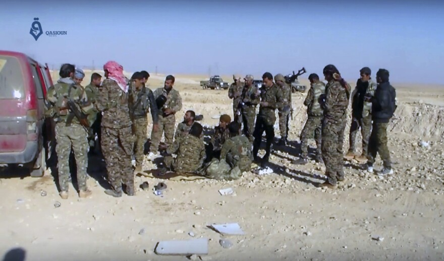 U.S.-backed fighters rest during fighting with the Islamic State group near Ein Issa, north of Raqqa, Syria, as shown in a video by Qasioun, a Syrian opposition media outlet.