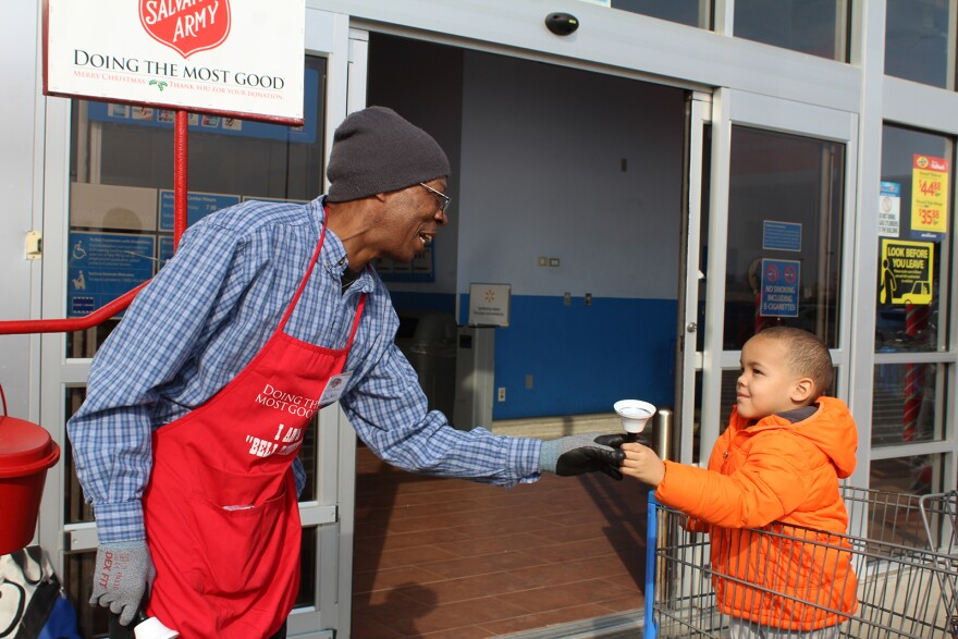 Salvation Army bell-ringer David Burks often lets children ring his bell and tell Santa Claus what they want for Christmas.