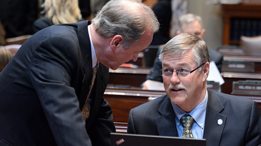 """State Sens. Warren Limmer (left) and Bill Ingebrigtsen talk in the Senate chamber. Limmer said he has been scolded for looking at his colleagues during debate before, and had """"to beg forgiveness to the Senate president."""""""