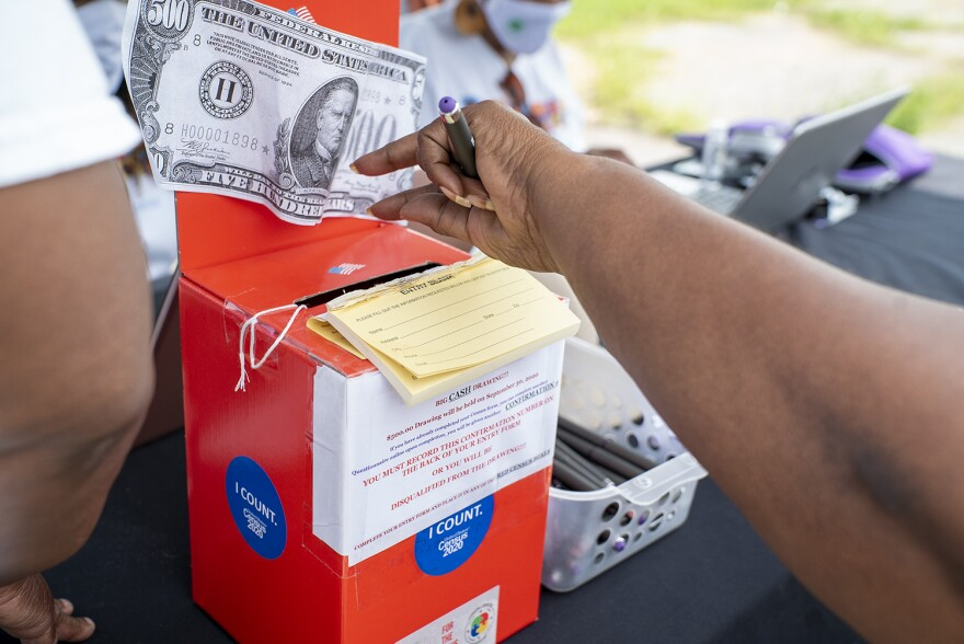 A Metro East resident submits a raffle ticket for $500 after filling out their census at a community event hosted by the Quad City Community Development Center in Venice, Ill. on Aug. 29. These red boxes appeared around Madison and Venice encouraging residents to respond to the census.