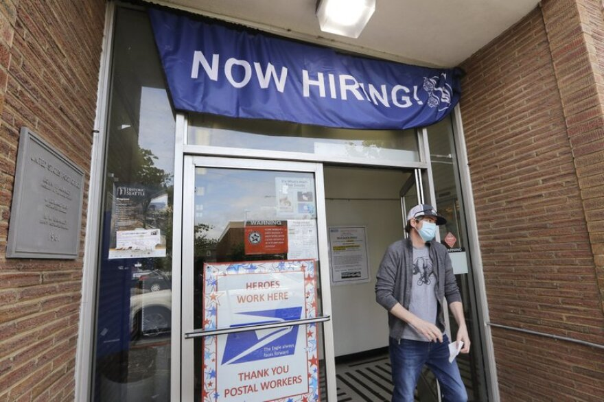 A customer walks out of a U.S. Post Office branch and under a banner advertising a job opening in Seattle.
