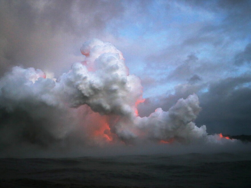 Steam plumes rise and lava glows as it enters the Pacific Ocean at dawn.