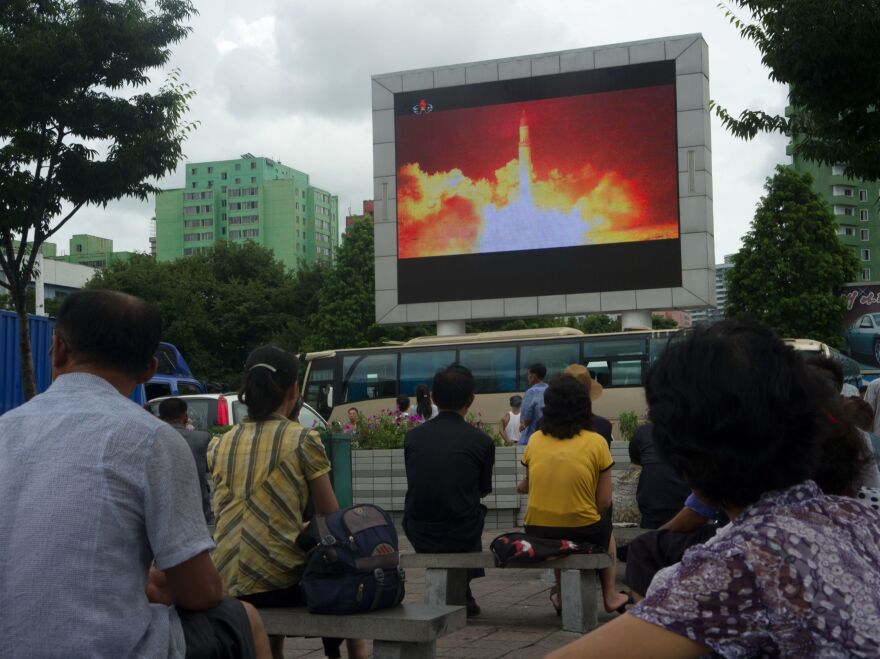 People watch as coverage of an ICBM missile test is displayed on a screen in a public square in Pyongyang on July 29, 2017.