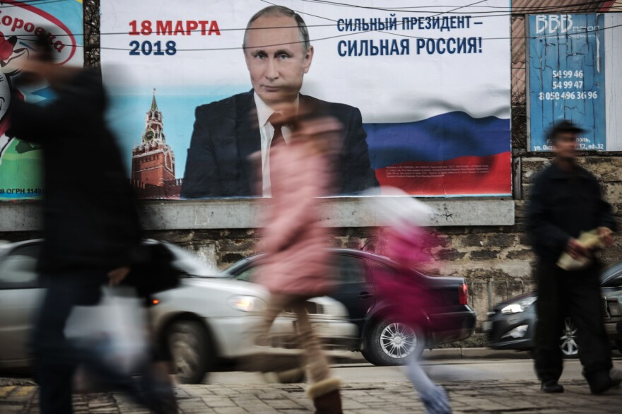 "Pedestrians pass by a billboard with an image of Russia's President Vladimir Putin and lettering ""Strong president - Strong Russia!"" in Simferopol, Crimea in January."