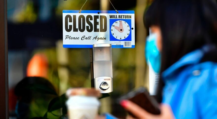 A pedestrian walks past a closed sign hanging on the door of a small business in Los Angeles, California.