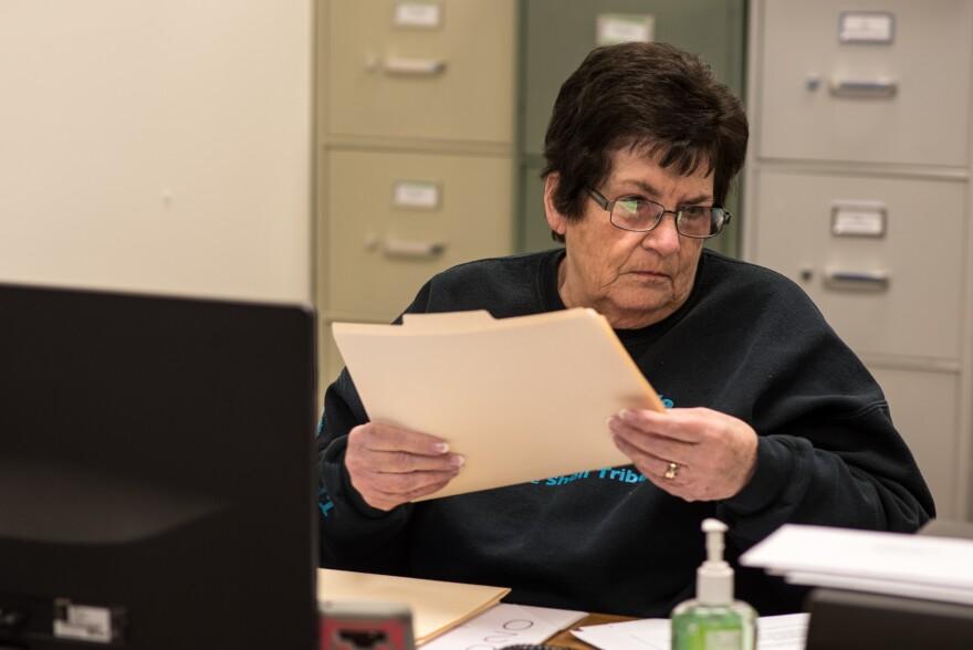 A photo of Linda Watson shuffling through Little Shell Tribe enrollment applications.