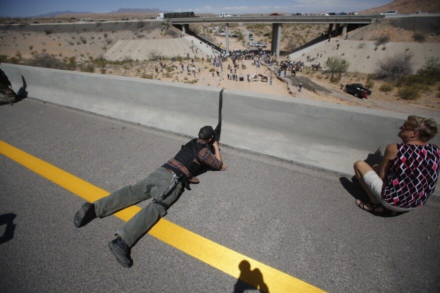 Eric Parker points his rifle from a bridge during an armed standoff with the federal government near Bunkerville, Nev., on April 12, 2014.