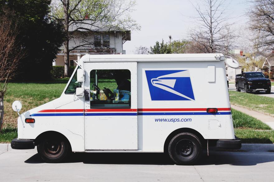 A United States Postal Service mail truck on a residential road.