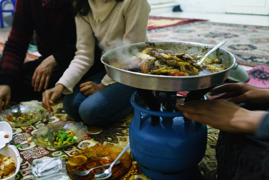 A Syrian woman cooks Aleppo-style kebab on a platter over a propane stove in her apartment in the southern Turkish city of Kilis, near the border with Syria, in December 2015.