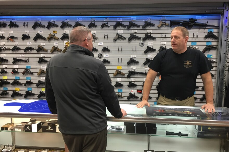 Paul Bastean speaks with a customer at his St. Peters firing range and gun store, Ultimate Defense.