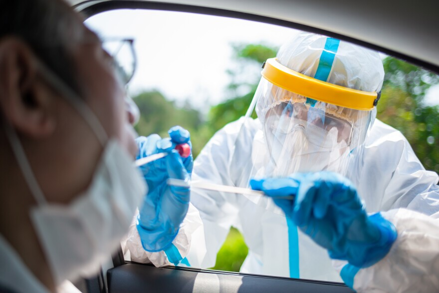 Stock image of a medical worker administering a COVID-19 test through the window of a vehicle