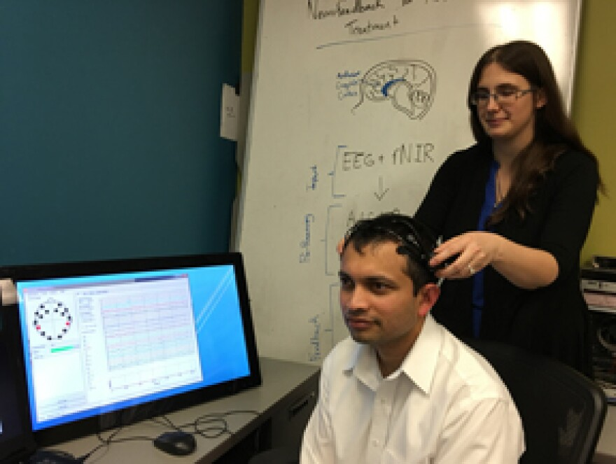 UDRI software engineer, Kelly Cashion (right), adjusts a wireless EEG headset on research engineer Nilesh Powar to demonstrate what a neurofeedback session would look like. Both work in the software systems group at UDRI.