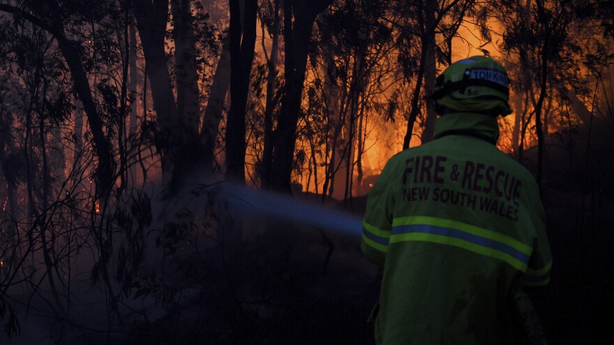 A firefighter battles a wall of flames Friday in Woodford, New South Wales.