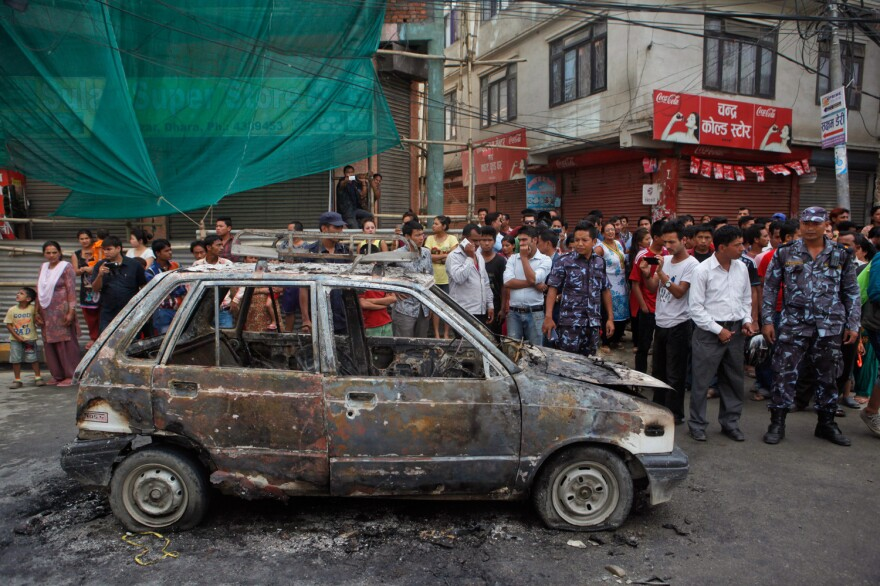 Demonstrators set fire to a car during a general strike in Kathmandu, Nepal. Police are in the blue uniforms.