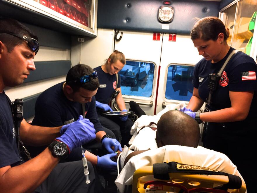 Emergency responders providing care to a patient in the back of an ambulance.